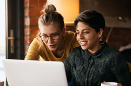 Two people looking at a laptop