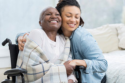 Photo of woman hugging her mother in a wheelchair