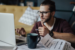 Image of a man on his laptop paying bills.