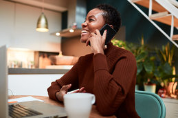 Woman at desk talking on cell phone