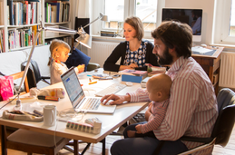 Photo of a family working at a dining room table