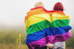 Photo of two individuals wrapped in a rainbow flag