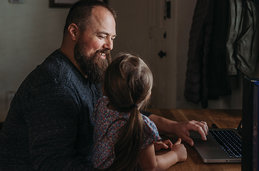 A father with daughter at a desk with a laptop