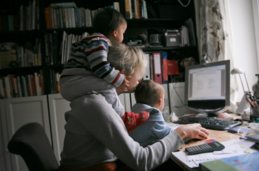 A mother working on her laptop while holding her children