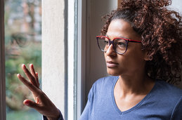 Photo of a Black woman at a window