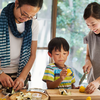 Photo of an Asian family slicing vegetables together in a kitchen