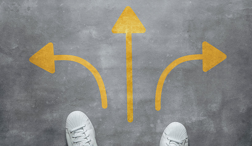 Shoes standing in front of directional arrows