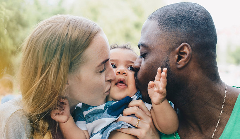 Photo of two parents kissing their baby