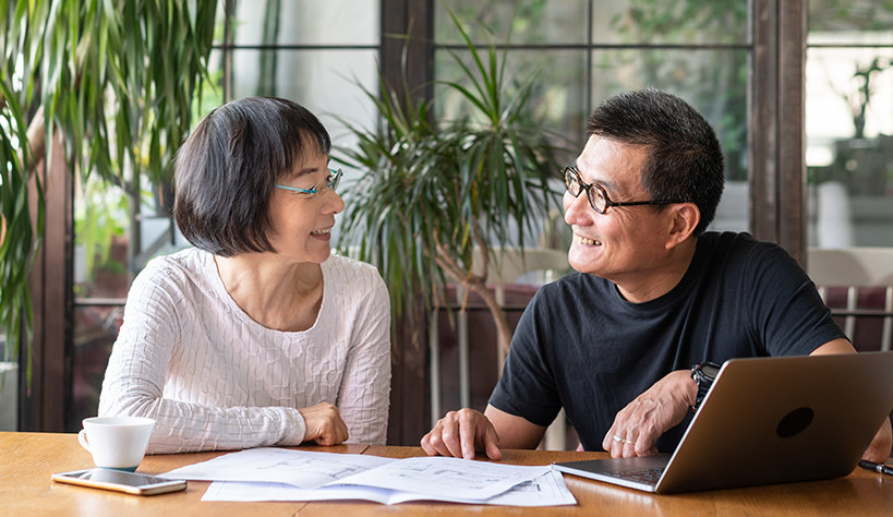A couple with a laptop and paperwork