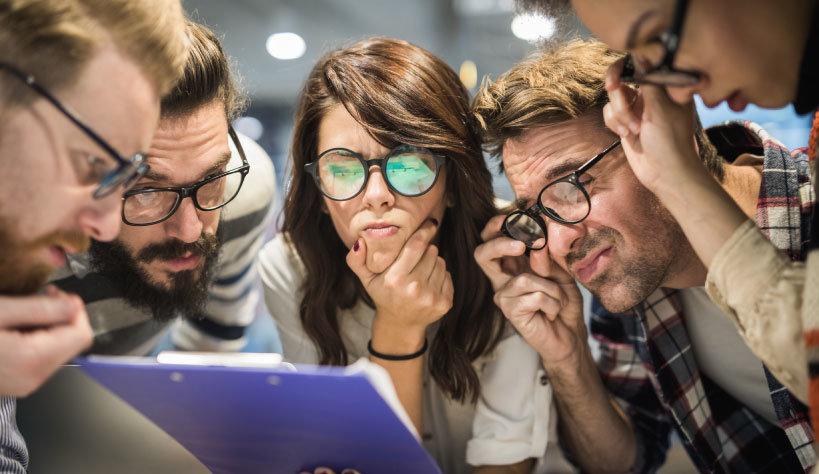 Photo of several people in glasses examining information
