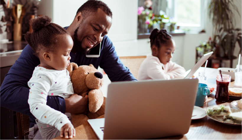 A father with his children at a dining table with a laptop