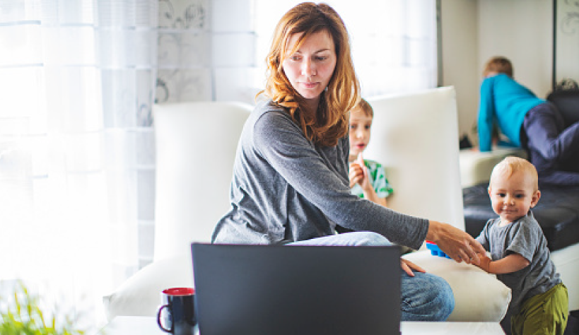 A woman on her computer with her young children