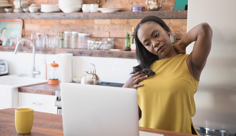 Photo of a woman stretching while working at home with her laptop