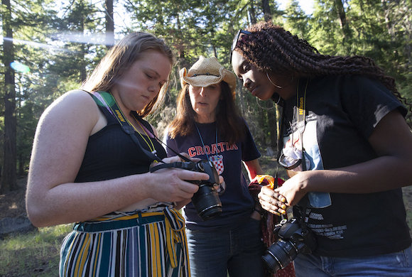 Photo of three people with cameras