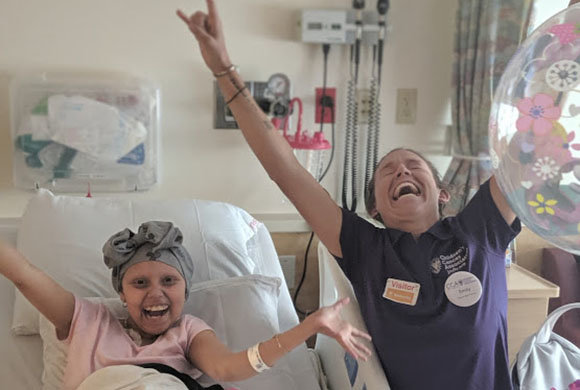 Photo of a girl patient and a doctor with arms raised joyfully