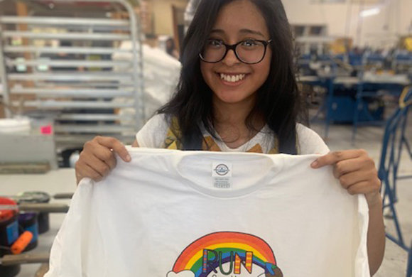 Photo of a girl holding up a rainbow t-shirt